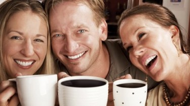 Three friends in a coffee house toasting with their cups
